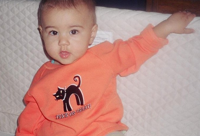 baby wearing an orange long sleeved shirt with Halloween heat transfers that say